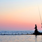 Silhouettes of two fishermen in the sea at sunset